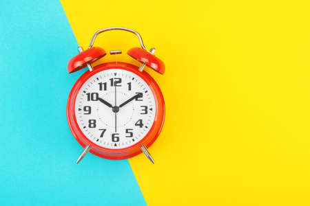 Red retro alarm clock with a big dial, on divided diagonally blue-yellow background. The concept of time, delay, morning rise, the appointed meeting. Layout with copy space for your text. Flat lay.
