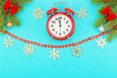 Christmas border with branches of spruce, snowflakes, christmas toys and alarm clock with five minutes to twelve oclock on a blue background. Layout with copy space for your text. Archivio Fotografico
