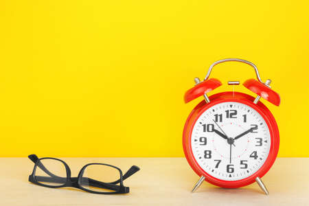 Red alarm clock and glasses on a wooden table against a yellow background. The concept of time, delay, morning rise, reading, poor eyesight. Layout with copy space for your text.
