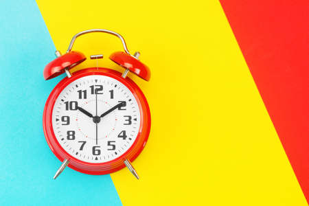 Red retro alarm clock with big dial, on divided diagonally blue-yellow-red background. The concept of time, delay, morning rise, the appointed meeting. Layout with copy space for your text. Flat lay.