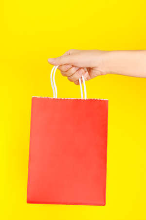 Hand holding red shopping or gift bag against yellow background. The concept of shopping or gifts.