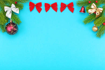 Christmas border with branches of spruce, holidays bows, christmas toys on a blue background. The concept of winter holidays. Layout with copy space for your text. Stockfoto