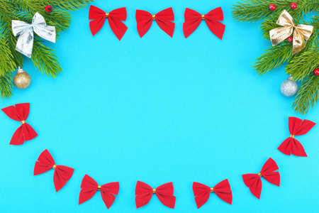 Christmas border with branches of spruce, holidays bows, christmas toys on a blue background. The concept of winter holidays: New Year, Christmas. Banco de Imagens