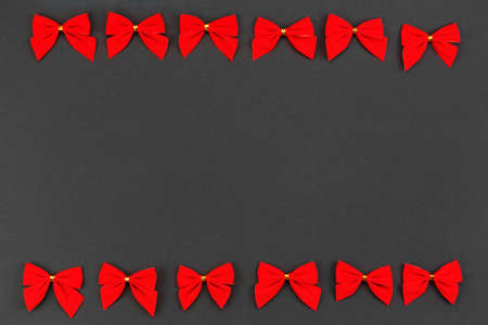 Two rows of red holiday bows on a black background.