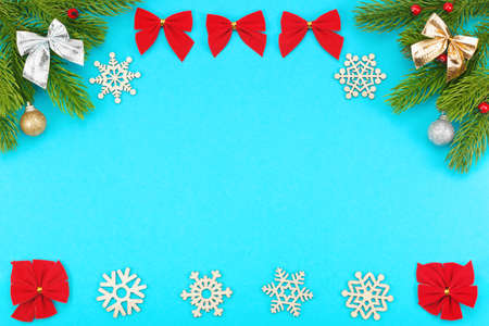 Christmas border with branches of spruce, snowflakes, holidays bows, christmas toys on a blue background. The concept of winter holidays: New Year, Christmas. Layout with copy space for your text. Banco de Imagens