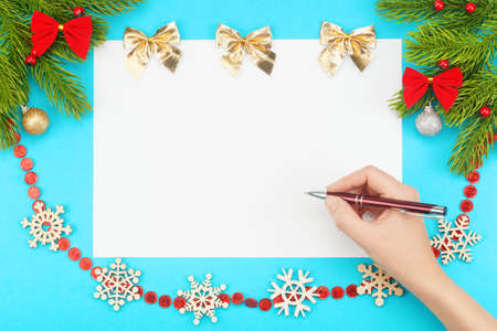 Hand with ballpoint pen over white blank paper with Christmas border consisting of branches of spruce, snowflakes, holidays bows, christmas toys on a blue background. The concept of winter holidays. Banco de Imagens