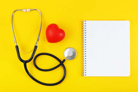 Red heart, stethoscope and blank note book on a yellow background. Health care concept, health worker, heart health care, medical care. Layout with a copy space for your ideas. Flat layout, top view.