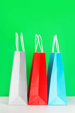 Colorful shopping or gift bags on wooden desk against green background. The concept of shopping or gifts. Layout with a copy space for your ideas.