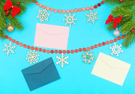Christmas border with branches of spruce, snowflakes, holidays bows, christmas toys and envelopes on a blue background. The concept of winter holidays, receiving letters and postcards with greetings.