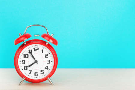 Red retro alarm clock with five minutes to eight o'clock, on wooden table on a blue background. The concept of time, holiday, 5 minutes to the event, deadline. Layout with copy space for your text. Standard-Bild
