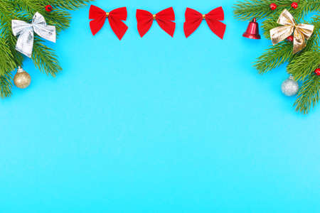 Christmas border with branches of spruce, holidays bows, christmas toys on a blue background. The concept of winter holidays. Layout with copy space for your text. Banco de Imagens
