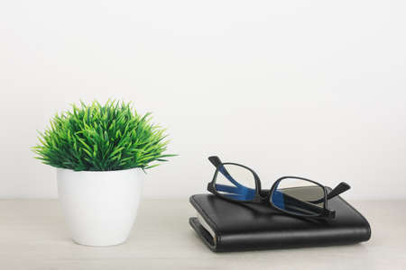 Artificial grass in a pot with glasses and notepad on a wooden table on a white background. The concept of office interior, home comfort, lifestyle. Mock-up with copy space for your text.