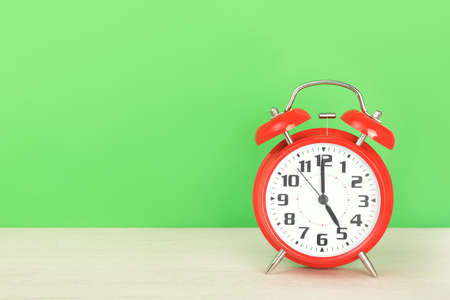 Red retro alarm clock with five o'clock, on wooden table on a green background. The concept of time, holiday, event start, deadline. Layout with copy space for your text. Standard-Bild