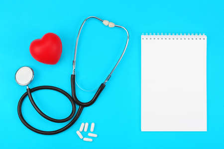 Stethoscope with blank notepad, red heart and white capsules on a blue background. Health care concept, health worker, heart health care, medical care. Flat layout, top view.