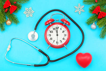 Branches of spruce, christmas toys, red heart with stethoscope and alarm clock with five minutes to twelve oclock on a blue background. The concept of Christmas holidays and medical care. Banco de Imagens