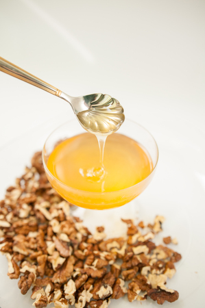 Honey natural with a wooden spoon on a white background