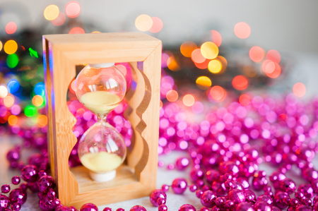 Christmas tree branches and pink balls on white background. Hourglass and New Year's gifts. Red necklace for Christmas decorations on spruce. Copy space