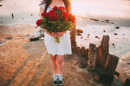 Girl in a hat with flowers at sunset