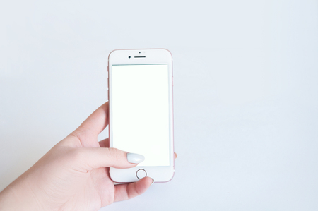 phone in hand with a white screen on a light background Stock fotó