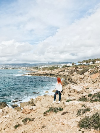 Red-haired girl on a deserted beach of stones by the sea. Autumn or spring. Reklamní fotografie