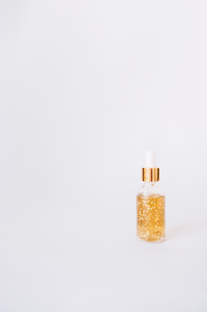 Cosmetic oil, serum with gold. Jar on a white background. Cosmetology. Youth.