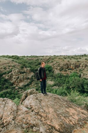 Young guy in nature. In the mountains of the canyon. Portrait of a man, mountain background Stock fotó