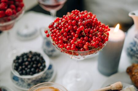Breakfast at home. Red currant in focus. Against the background of berries, coffee, honey, croissants, cheese. Beautiful serving.