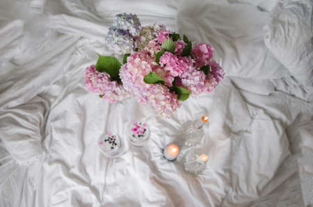 Blue-pink beautiful hydrangea (hortensia) bouquet in bed. Ice with petals.