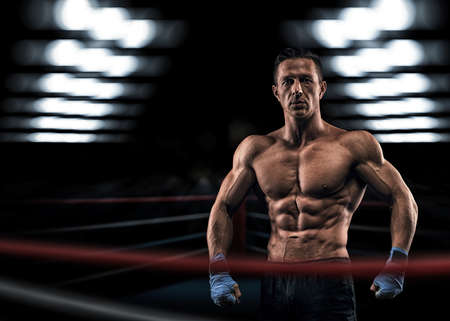 asian abs: A strong man in the ring in blue boxing bandages preparing for battle Stock Photo