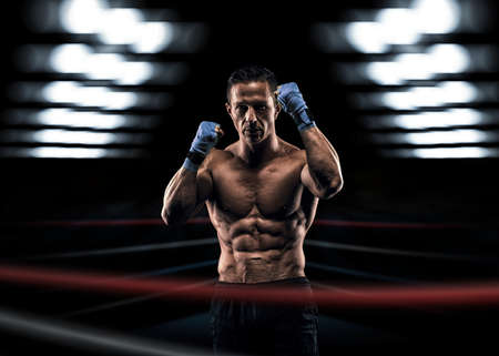 boxing knockout: A strong man in the ring in blue boxing bandages preparing for battle Stock Photo
