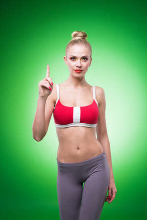 laying abs exercise: Young sports sexy girl in the studio on a green background shows the various movements
