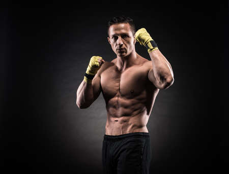 exercise man: Muscular young man in boxing gloves and shorts shows the different movements and strikes in the studio on a dark background Stock Photo