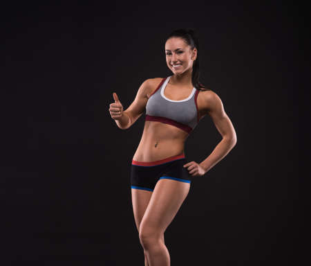 Young sportslooking nice lady with dark hair on the black background in studio