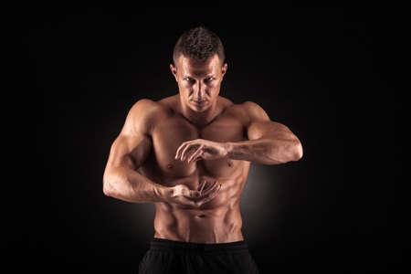 Sexy muskulöser Kerl im Studio zeigt die verschiedenen Bewegungen