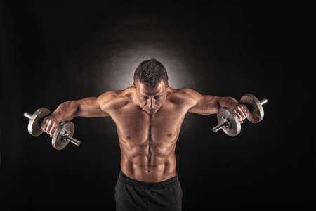 Handsome Strom sportlichen Mann Bodybuilder machen Übungen mit Hanteln. Fitness muskulösen Körper auf dunklem Hintergrund.