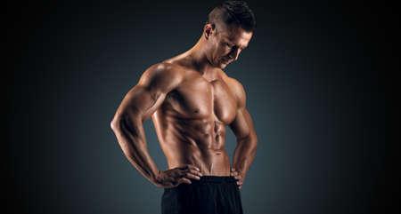 Muskulöser junger Mann im Studio auf dunklem Hintergrund zeigt die verschiedenen Bewegungen und Körperteile