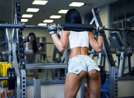 fitness abs female: young sexy girl in a sports gym shorts and Tshirt for sports