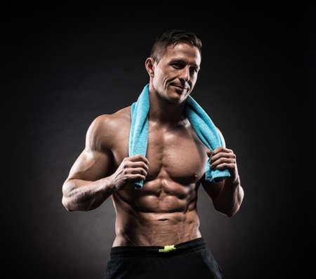 어두운 배경에 스튜디오에서 근육 질의 젊은 남자가 다른 움직임과 신체 부위를 보여줍니다.