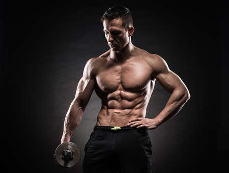 culturista: Poder guapo hombre atl�tico culturista haciendo ejercicios con mancuernas. Musculoso cuerpo fitness en el fondo oscuro.