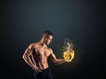 Handsome power athletic man bodybuilder doing exercises with dumbbell. Fitness muscular body on dark background.