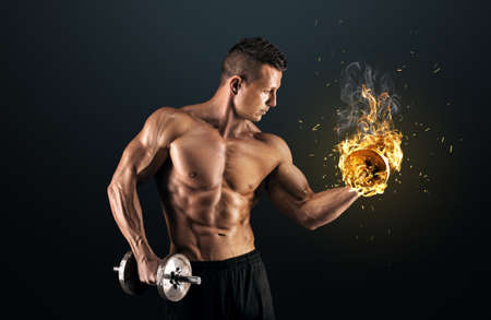 Handsome power athletic man bodybuilder doing exercises with dumbbell. Fitness muscular body on dark background. photo