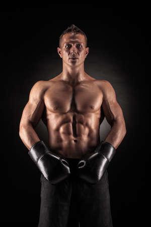 Muskulösen jungen Mann in Boxhandschuhe und Shorts zeigt die verschiedenen Bewegungen und Streiks im Studio auf einem dunklen Hintergrund