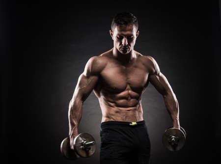 아령으로 운동을하는 잘 생긴 전원 체육 남자 보디. 어두운 배경에 피트니스 근육질 몸.