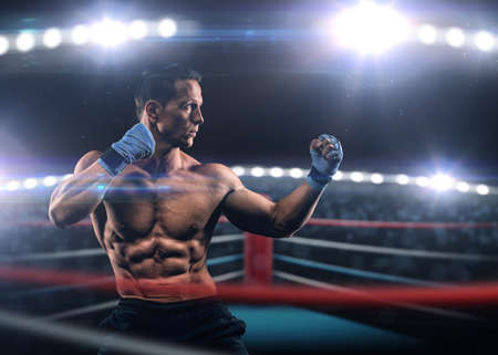 A strong man in the ring in blue boxing bandages preparing for battle Stock Photo