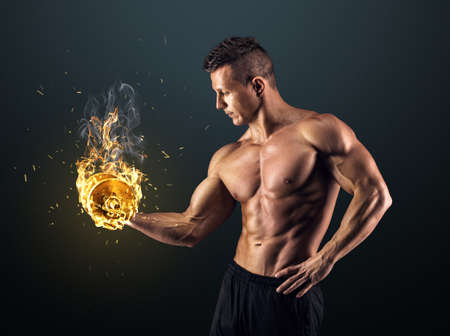 atletismo: Poder guapo hombre atlético culturista haciendo ejercicios con mancuernas. Musculoso cuerpo fitness en el fondo oscuro.