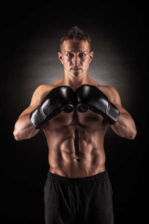 Muscular young man in boxing gloves and shorts shows the different movements and strikes in the studio on a dark background Standard-Bild
