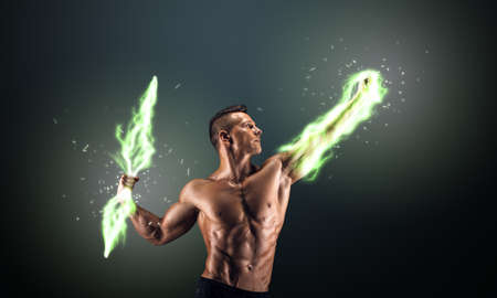 burning man: Muscular guy on dark background controls lightning Stock Photo