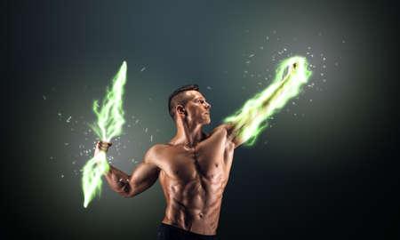Muscular guy on dark background controls lightning Stock Photo
