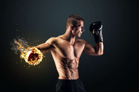 Muscular young man in boxing gloves and shorts shows the different movements and strikes in the studio on a dark background photo