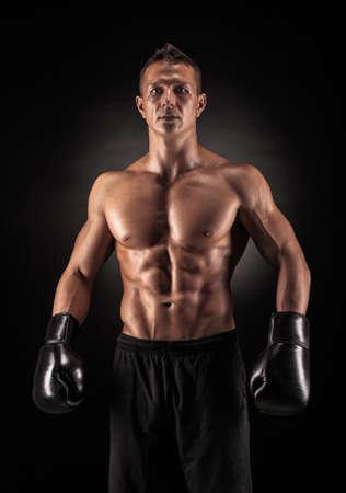 권투 장갑과 반바지에 근육 젊은 남자가 어두운 배경에 스튜디오에서 다른 움직임과 공격을 보여줍니다